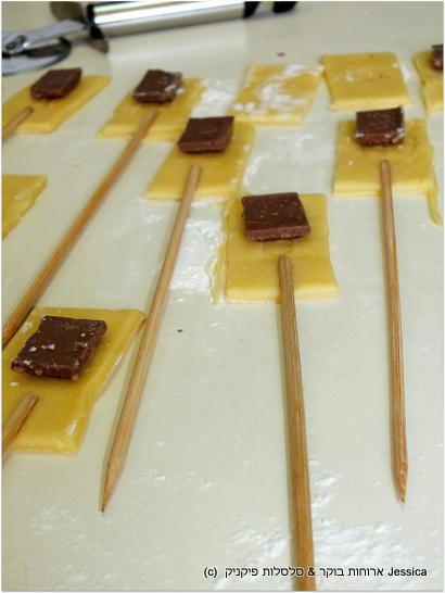 להכניס שיפוד בחלק התחתון של הריבוע, שייגע בקוביית השוקולד